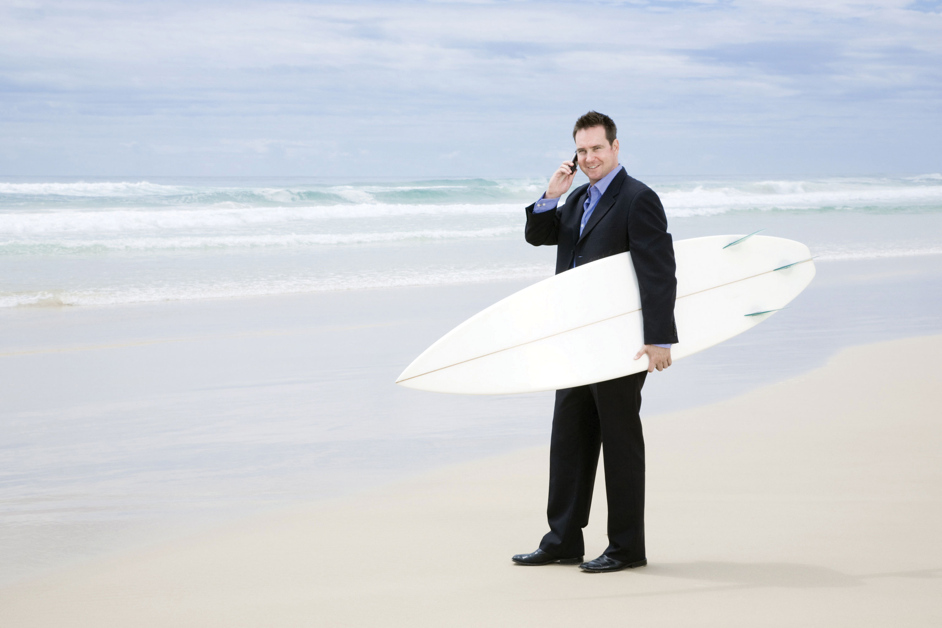 Shellharbour-man in suit with surfboard